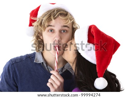 Christmas kiss, young girl kisses her boyfriend as he sucks on a candy cane - stock photo