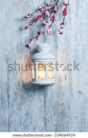 Christmas lantern and snow on wooden background