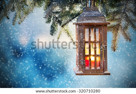 Christmas lantern hanging on fir branches at night