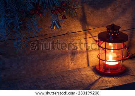 Christmas lantern in night on old wooden background.