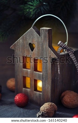 Christmas lantern in shape of small wooden house with  candle inside - stock photo
