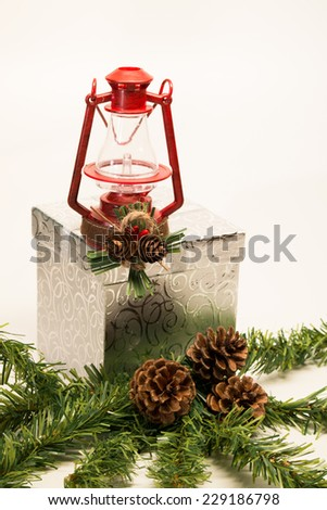 Christmas Lantern Small red Christmas lantern placed on a shinny silver gift, with pine cones and evergreen branches surrounding the gift box. - stock photo