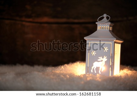 Christmas lantern with a decorative cut out pattern of a reindeer standing on a bed of fresh winter snow glowing in the night as a welcoming light, with copyspace for your seasonal greeting - stock photo