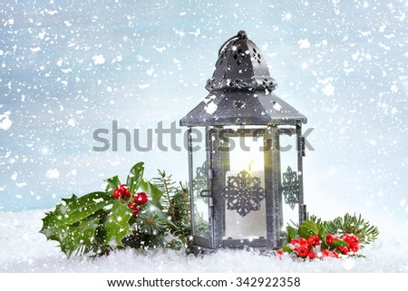 Christmas lantern with Holly leaves and berries on a snowy background. - stock photo