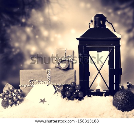 Christmas lantern with presents, ornaments and snow in sepia tone - stock photo
