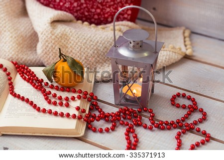 Christmas Lanterns,  mandarin and red beads on wooden background.