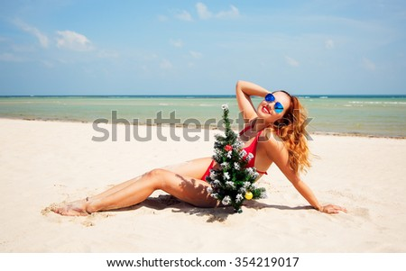 Christmas lifestyle portrait of pretty tanned woman lying on the beach. Smiling girl is posing near Christmas tree. Wearing stylish red bikini and sunglasses. Sporty slim body and long beautiful legs