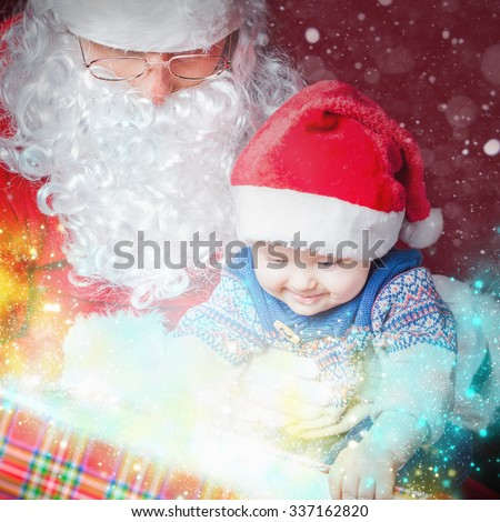 Christmas light and inspiration! Christmas baby wearing a Santa Claus hat and Santa opening a present and gift box! Night, xmas eve, surprise. Magical light. Design - stock photo