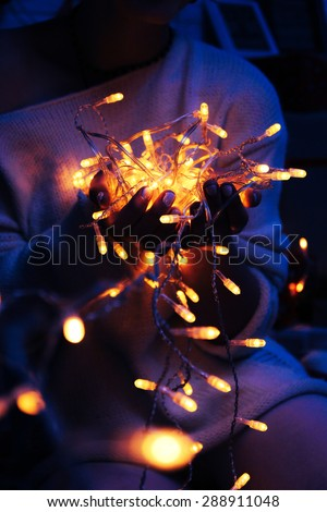 Christmas light bulbs in hands - stock photo
