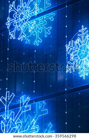 Christmas lights decoration on a building facade in blue tone. Vertical - stock photo