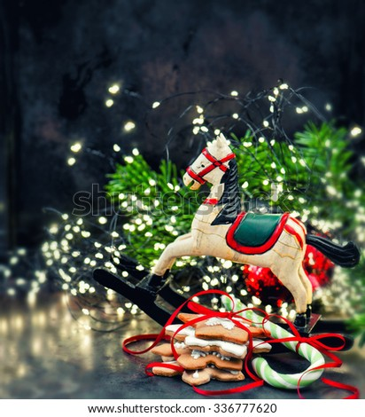 Christmas lights decoration, rocking horse and cookies. Retro style toned picture. Selective focus - stock photo