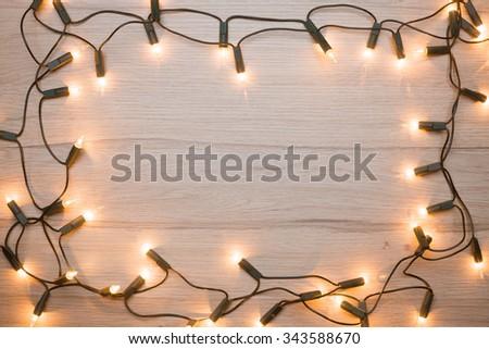 Christmas lights  frame on a wood - stock photo