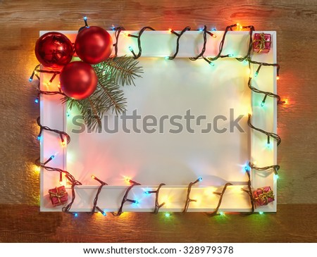 Christmas lights frame on wooden background with copy space. Decorative garland - stock photo