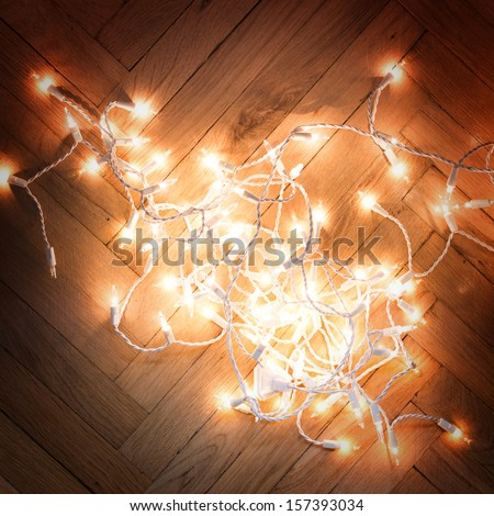 Christmas lights garland on a old antique wooden parquet floor,  - stock photo