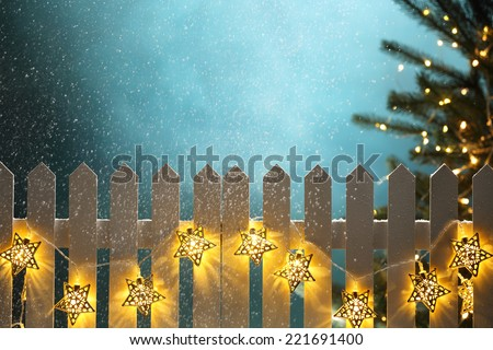 Christmas lights hanging on fence at snowy night,Christmas concept. - stock photo