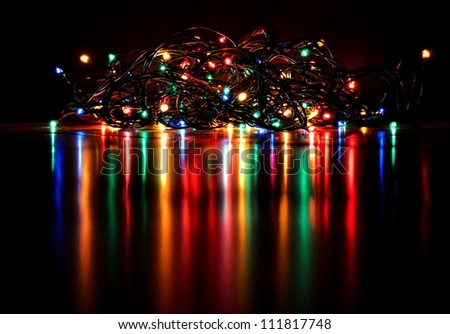 Christmas lights on a tree with a beautiful reflection and black background - stock photo