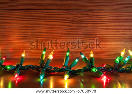 christmas lights on a wooden shelf with natural wood background