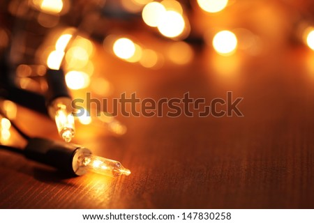 Christmas lights on dark wooden background - stock photo