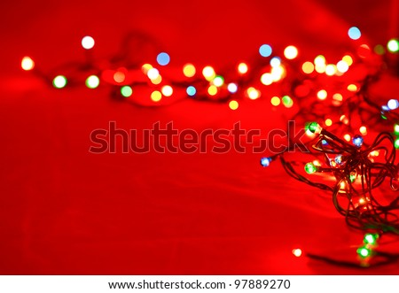 Christmas lights on red background, shallow focus - stock photo