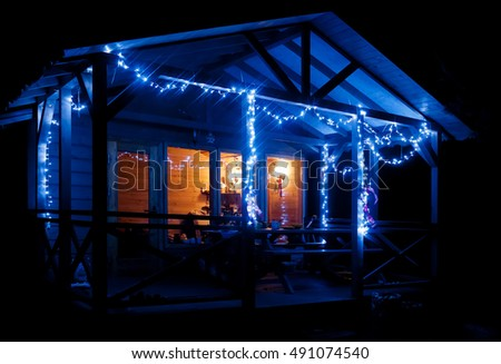 Christmas lights. Small wooden lodge with a terrace is decorated with a Christmas lights