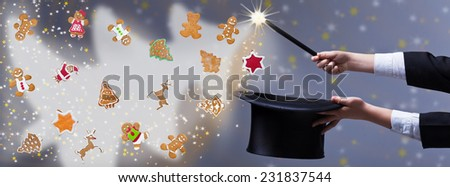 Christmas magic with gingerbread cookies - magician hands holding black hat and wand - stock photo