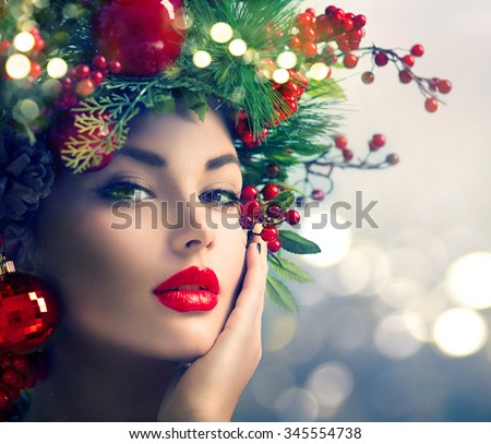 Christmas Makeup. Winter Fashion Woman. Beautiful New Year and Christmas Tree Holiday Hairstyle, Make up. Beauty Model Girl over glowing Background. Creative Hair style decorated with Baubles  - stock photo