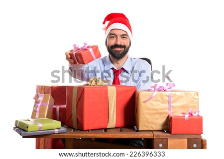 Christmas man in his office with several gifts