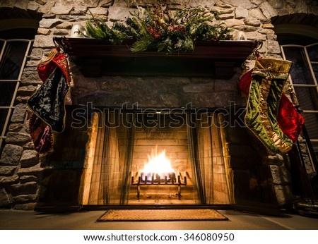 Christmas Mantle above Lit Fireplace with Stockings Hanging - stock photo