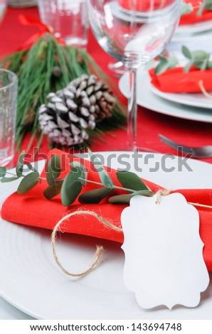 Christmas meal table setting with red napkins tied in twine ribbon and branch, pine cone and green centerpiece - stock photo