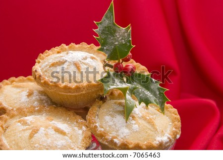 Christmas mince pies with holly and berries dusted with icing sugar on red tablecloth