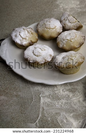 Christmas mince pies with icing on the white ceramic plate - stock photo