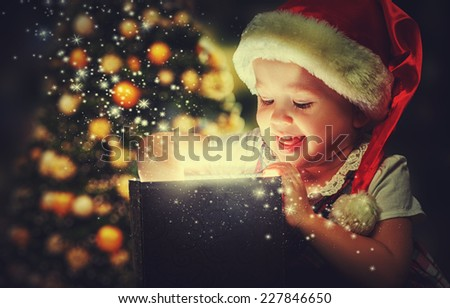 Christmas miracle, magic gift box and a child baby girl  - stock photo