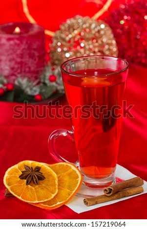 christmas morning tea served in a tall clear glass with spices and a red table cloth