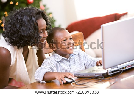 Christmas: Mother And Son Online At Christmas Time  - stock photo