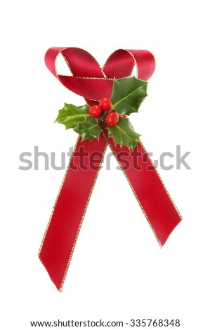 Christmas motif, gold edged red ribbon bow with a sprig of Holly isolated against white - stock photo