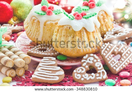 Christmas muffins, gingerbread cookies with icing hearts, colorful candies and sweets on the festive table - stock photo
