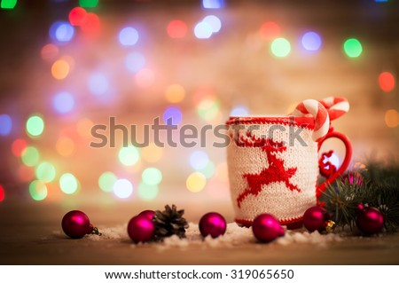 Christmas mug with decorations and sweets on wooden background - stock photo