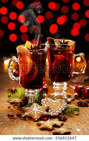 Christmas mulled red wine with the addition of spices and oranges on a wooden table