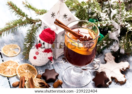 Christmas mulled wine with lemon slice, anise and cinnamon sticks and snowman - stock photo