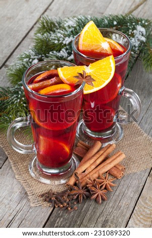 Christmas mulled wine with spices and snowy fir tree on wooden table - stock photo