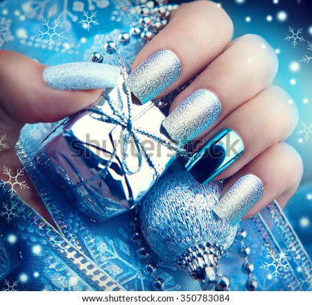 Christmas Nail art manicure. Winter Holiday style bright Manicure Design. Christmas decorations and snowflakes. Nail Polish. Beauty hands. Trendy Stylish Silver and Blue Colorful Nails, Nailpolish - stock photo