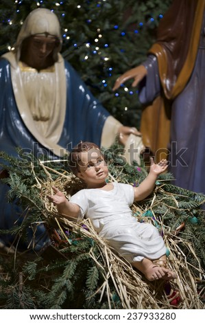 Christmas nativity scene with Mary and Joseph looking down on baby Jesus in his manger - stock photo