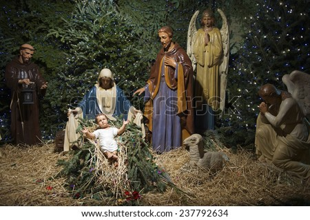 Christmas nativity scene with Mary, Joseph, and the Angel Gabriel looking down on baby Jesus in his manger - stock photo