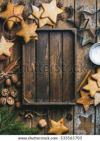Christmas, New Year background. Gingerbread cookies, sugar powder, nuts, spices, baking molds, fir-tree branch, decorative rope on wooden background, rustic tray in center, top view, copy space