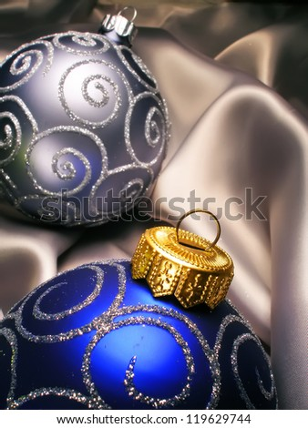 Christmas New Year balls on silk background. Light and dark blue Christmas decoration on milky silk.