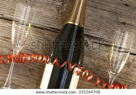 Christmas, New Year, Celebration, Champagne in a glass bottle, glasses, tree, bells, streamers, Top view, closeup. - stock photo