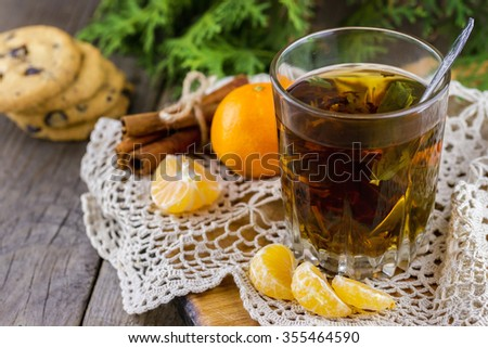Christmas (New Year) composition. Glass cup of tea with mint, tangerine slices, cinnamon sticks, chocolate chip cookies and thuja branches on wooden background - stock photo
