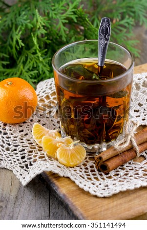Christmas (New Year) composition. Glass cup of tea with mint, tangerine slices, cinnamon sticks and thuja branches on wooden background - stock photo