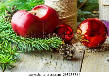 Christmas (New Year) decoration composition. Close-up view of  fur-tree branches, heart candle, red glass balls and cones on wooden background