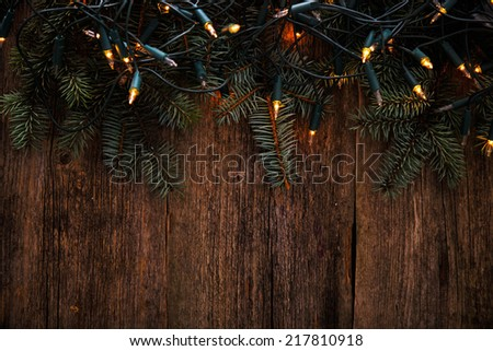 Christmas, New Year. Fir with garland on a wooden table - stock photo